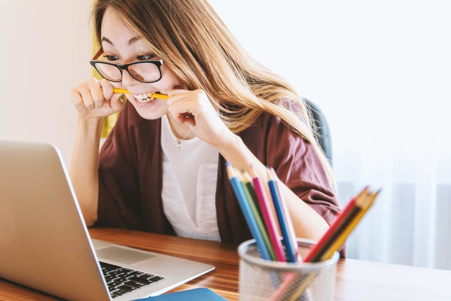Woman biting pencil in frustration at laptop