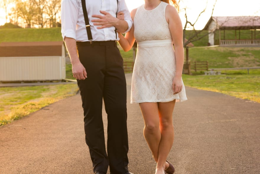 A young couple walk down a country lane arm-in-arm, with their faces not visible.