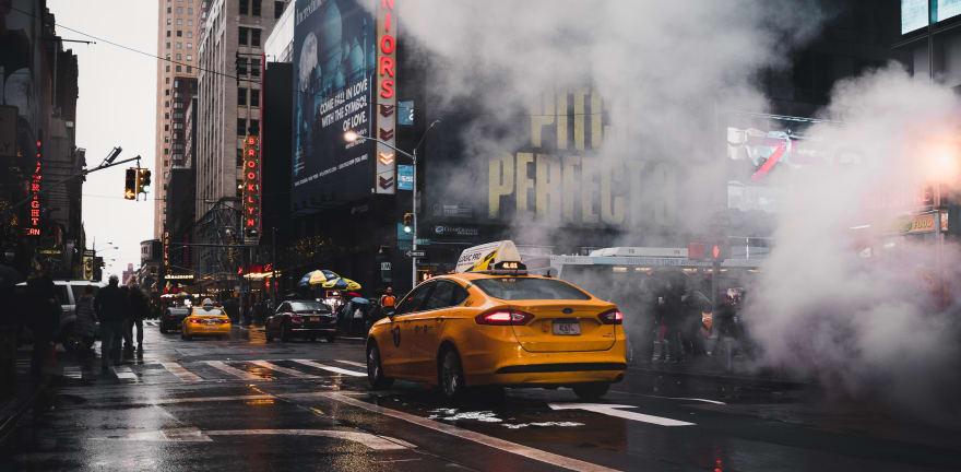 New York Taxi driving down 7th Avenue through a cloud of steam