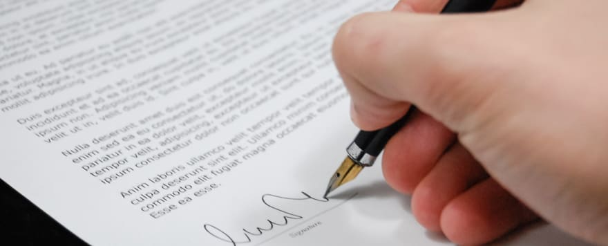 Image of hand signing a legal document