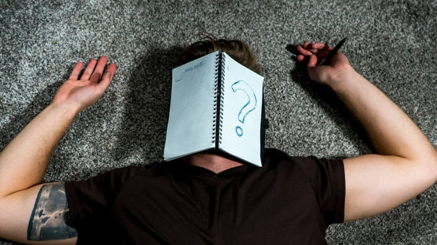 Image of man lying on the floor with a paper with a question mark drawn on it covering his face