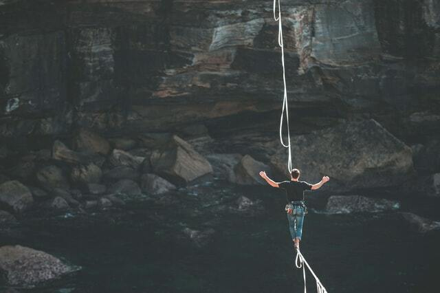 Man walking on tightrope over canyon