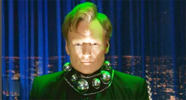 Conan O'Brien, lit by green light, with a futuristic collar with regularly spaced hemispheres protruding from it