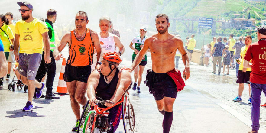 Photography showing different runners in a race. One of them is in a wheelchair