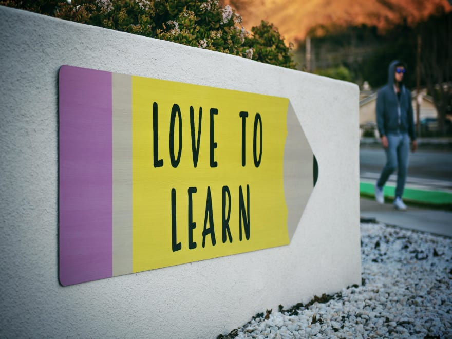 Picture of a wall with an art saying Love to Learn