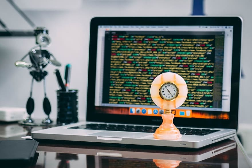 a clock standing on laptop with a lot of code on the screen