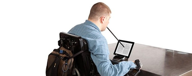 Photo of a person using a mouth-held stylus to operate a screen