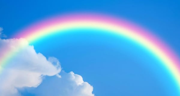 bright rainbow over white clouds on the left and a sunny blue sky