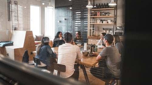 People in a meeting behind glass door