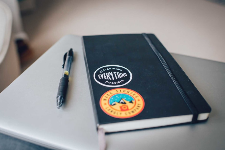 """Hardcover Moleskine notebook with """"Design makes everything possible"""" sticker and pen on table"""