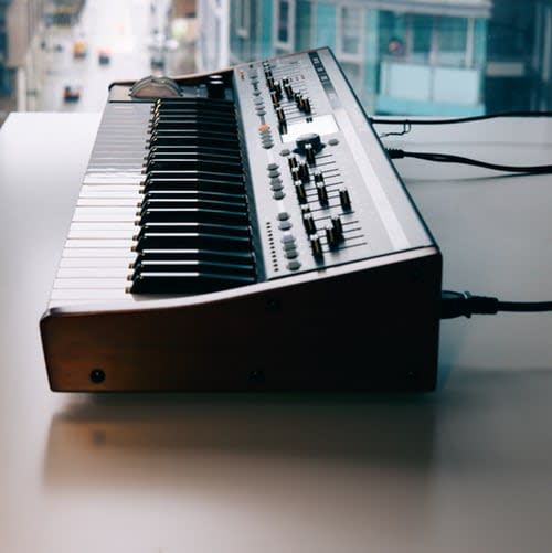 A picture of a midi keyboard as seen from the side, sitting by a window, on a table. An empty street can be seen in the background.