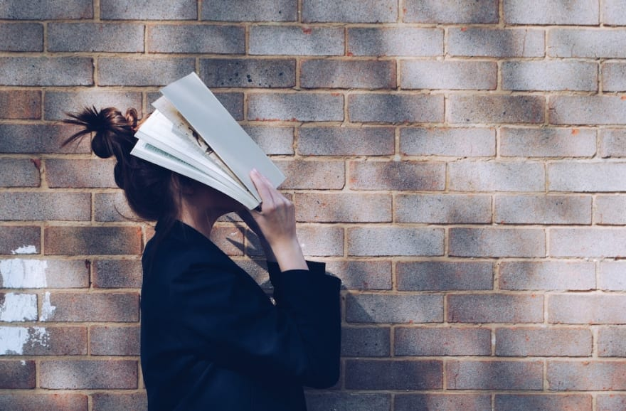a girl hitting her face with a book