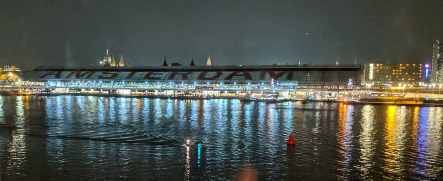 Photograph of Amsterdam station at night reflecting on the water