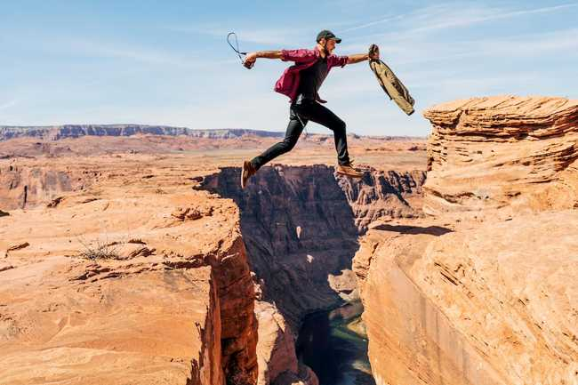 Photo of a man carelessly leaping over a very deep chasm by Alex Radelich