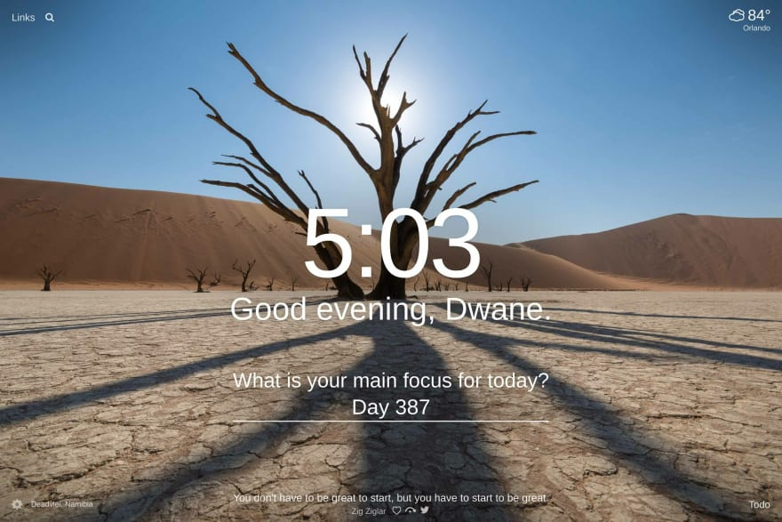 A tree with no leaves and the sun behind it casting a shadow in the desert of Deadvlei, Namibia with sand dunes in the background.