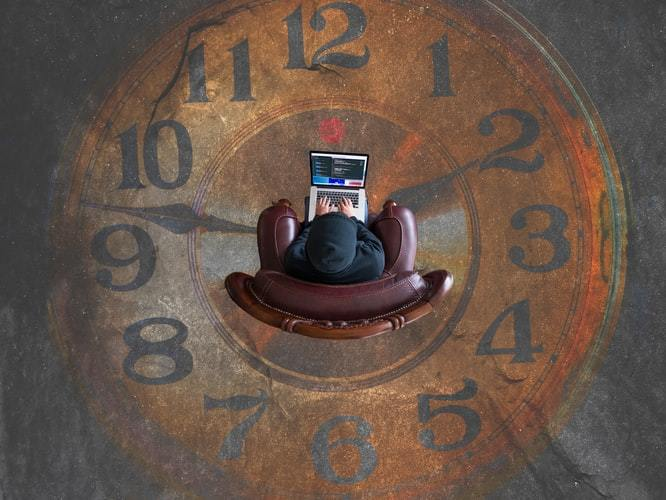 Man working on a laptop, sitting on a clock surface