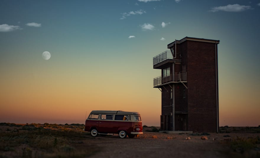 Photo called 'Feel the freedom' in Dungeness, United Kingdom, displaying a red Volkswagen Samba parked near brown house.