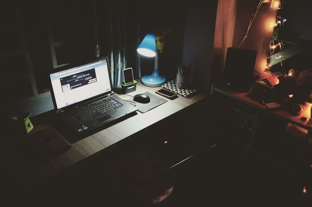 a poorly lit laptop screen and lamp