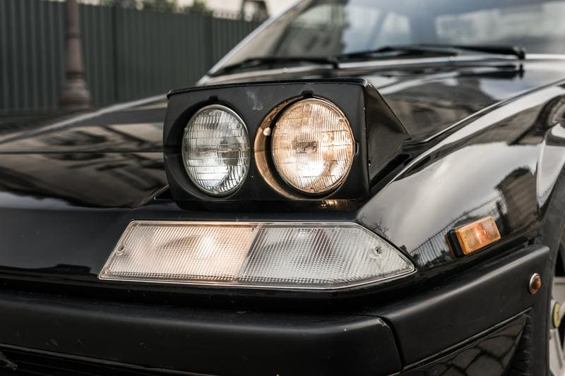 A closeup to the front lights of an old Ferrari