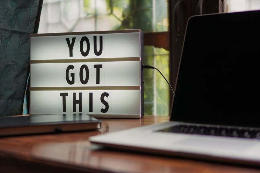 """A laptop and a book on a table, with a light-up sign that says """"You Got This"""""""