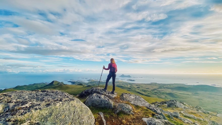 Person with hiking sticks overlooking a landscape on top of a mountain