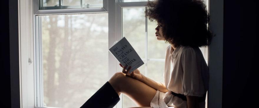Mulher preta lendo livro sentada na janela