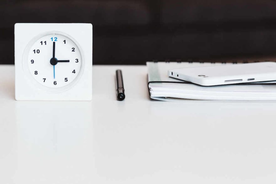 A clock, pen, planner, and smartphone on a white desk
