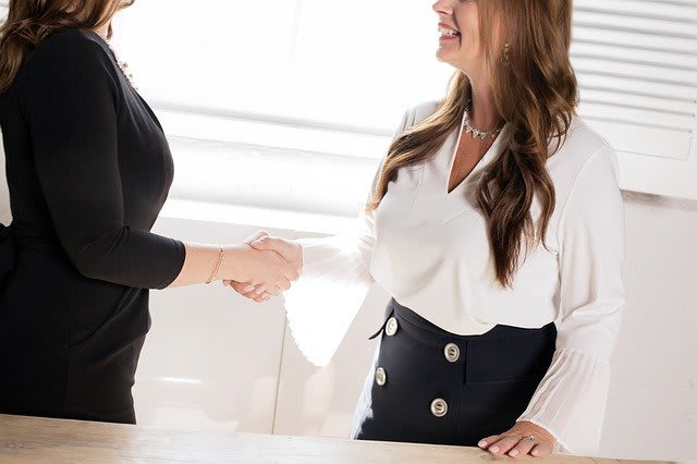 Two women shaking hands, presumably after an interview has just ended