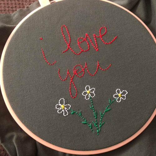 "My second embroidery piece ever that reads ""I love you"" in red cursive and has three white flowers below the words."