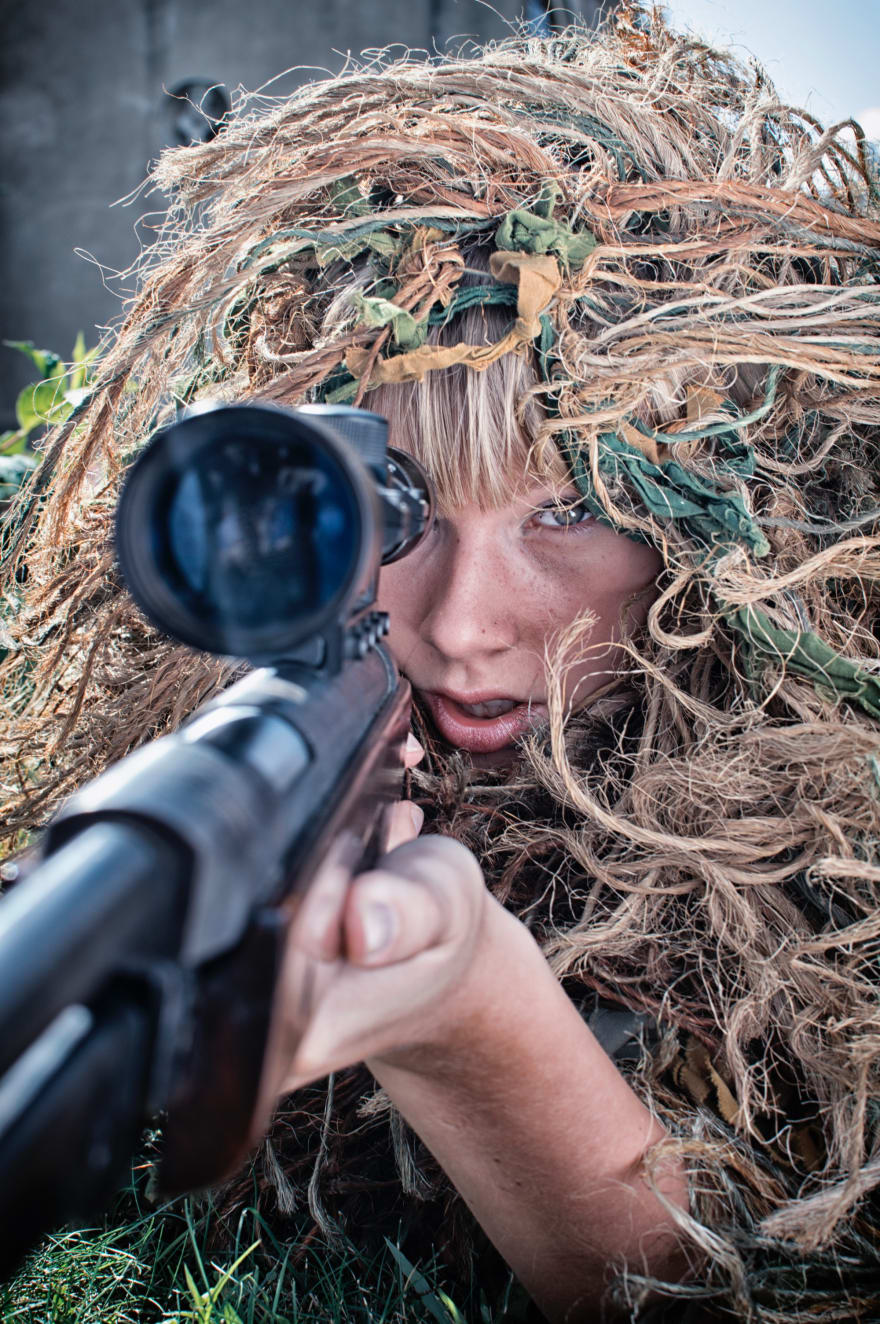 A female sniper is camouflaged and aiming her rifle