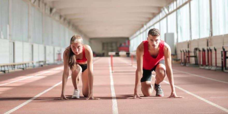 A young woman and a young man athletes prepare to run in a training hall