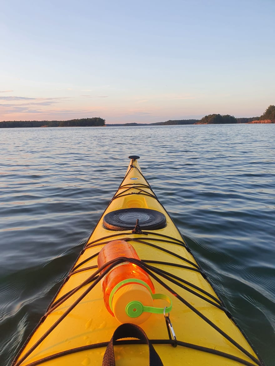 A view from a kayak showing the front of the yellow kayak and water surrounding it. There are land and some trees in the distance.