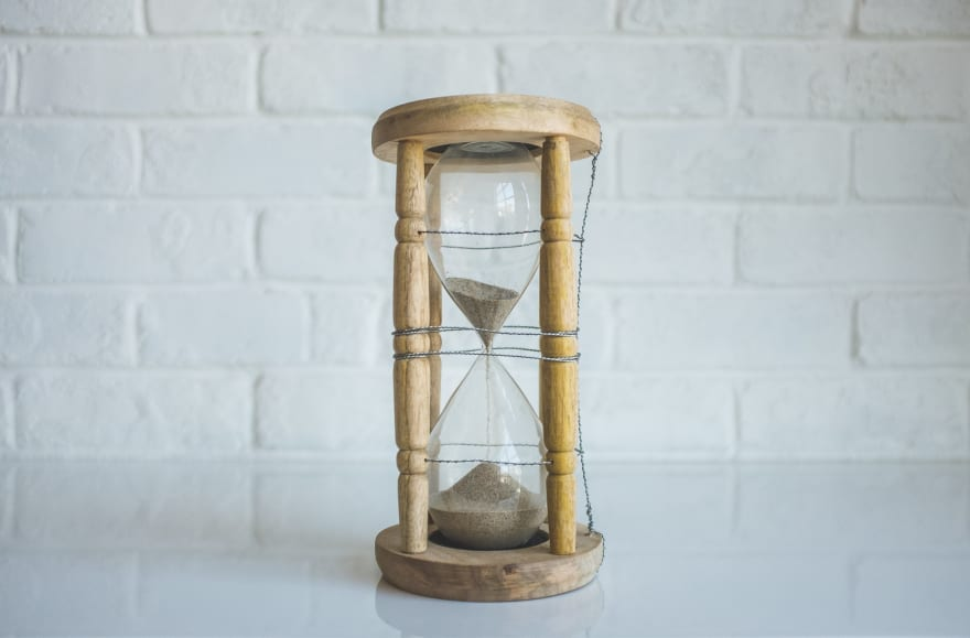 A wooden hourglass with light brown sand sitting on a white tabletop surface against a white exposed brick wall