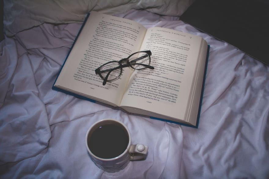 A book set on top a bed with a pair of folded reading glasses on the book. Nearby is a laptop and a cup of coffee.