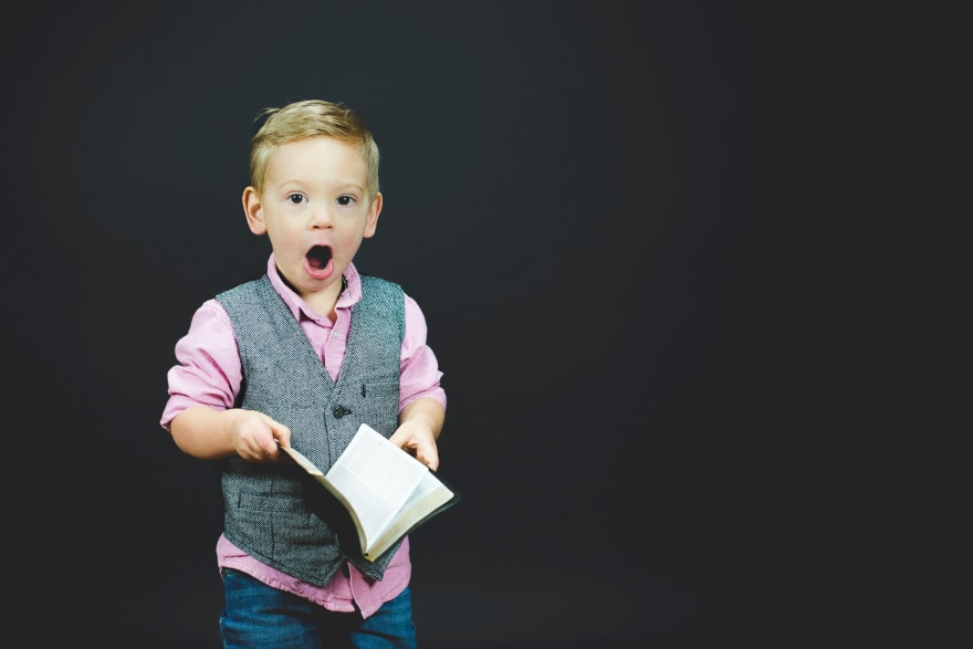 A boy holding a book with his mouth open in wonder.