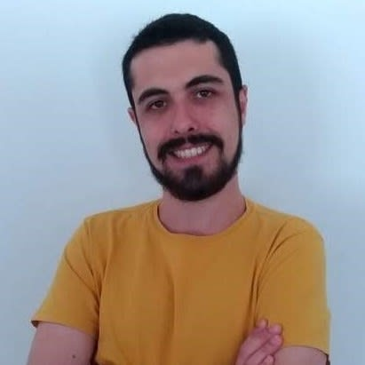 Albert's profile picture, smiling with a yellow shirt and crossed arms