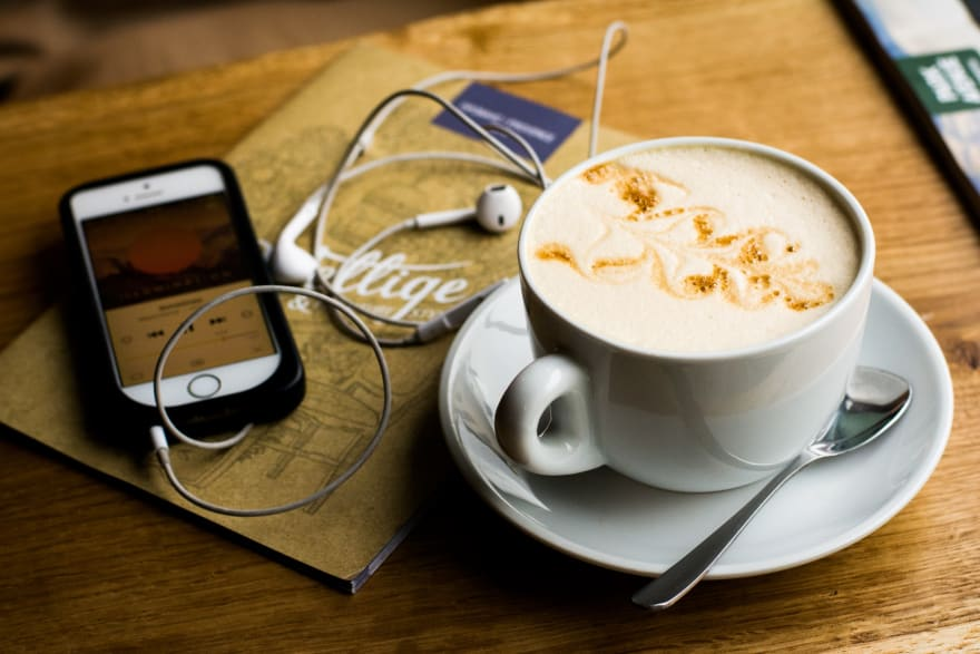 image showing a cup of coffee and a phone with earbuds and a podcast client open