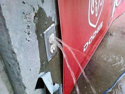 A power socket in a wall with water streaming out