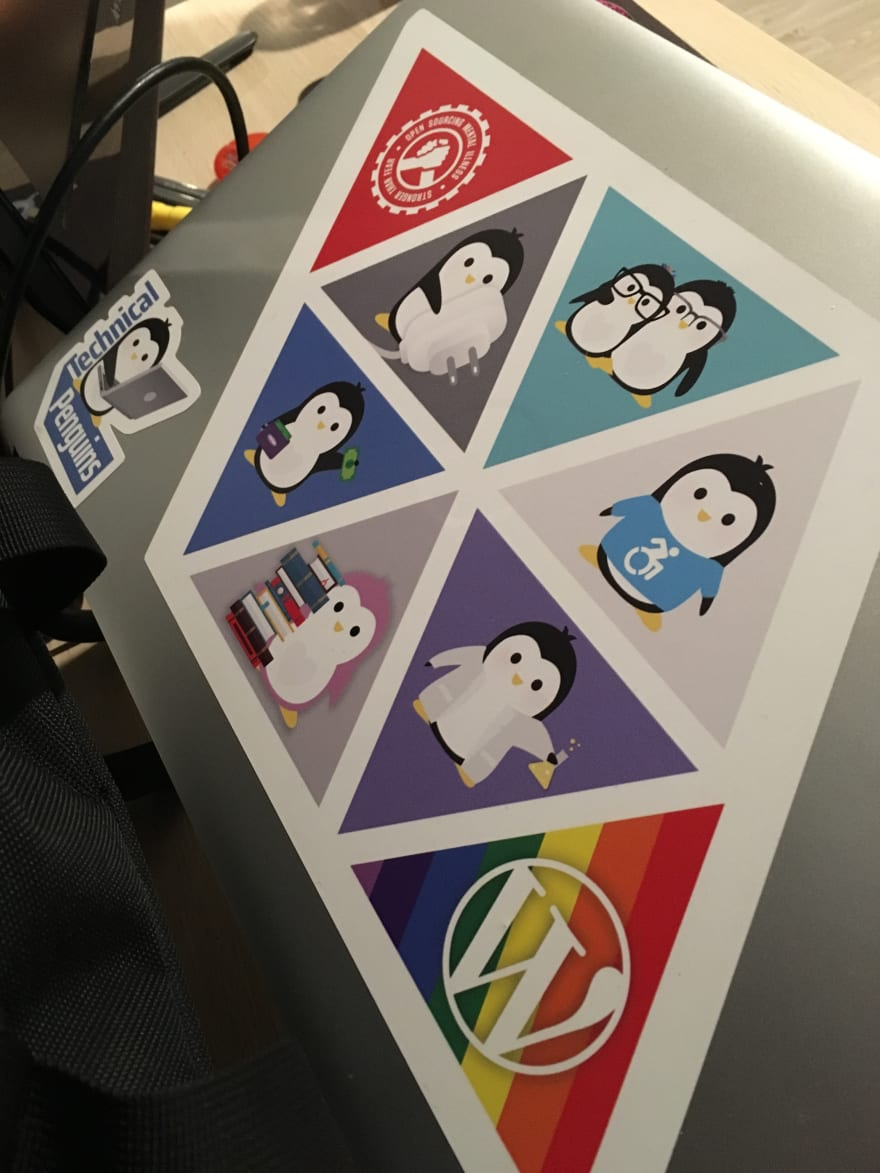 A Technical Penguin sticker-covered laptop