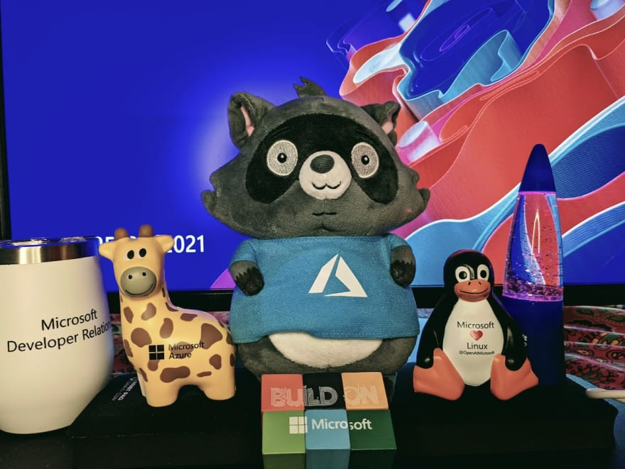 Image with a coffee mug, a giraffe mascot, a stuffed raccon, a penguin and a mini lamp:left::round