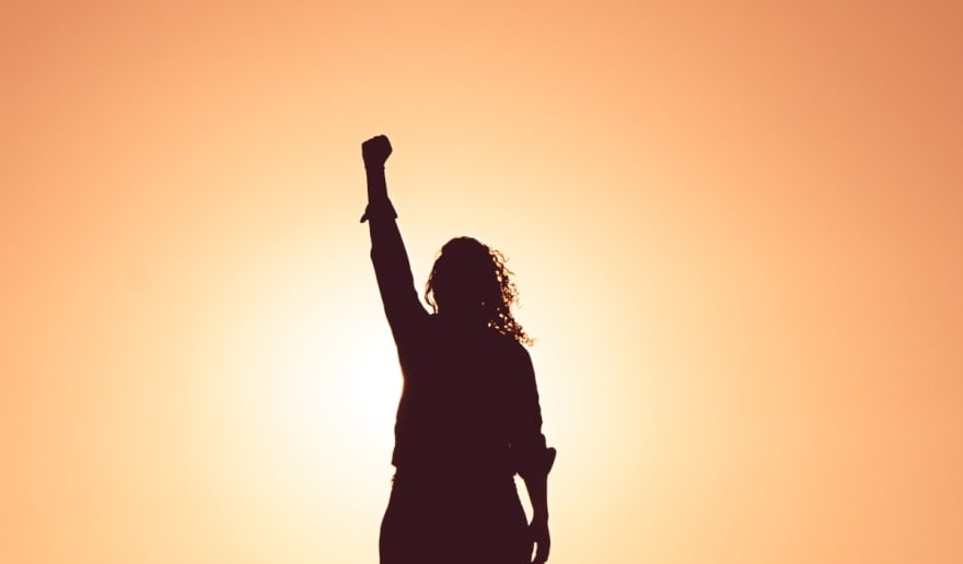 Woman holding her hand in the air in front of a sunset