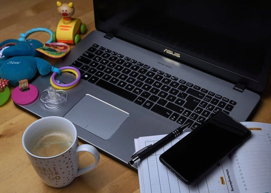 """Open Asus laptop covered with baby toys, a calendar, a cellphone. In the foreground is a coffee mug with the words """"Sparkle wherever you go"""""""