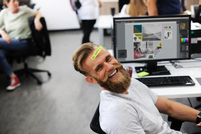 "A man smiling near his computer. A sticky-note with the words ""Be Happy"" is stuck on his forehead."