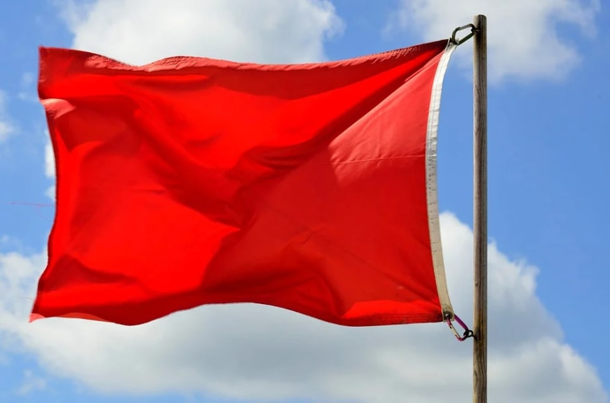 large red rectangle flag on wooden pole