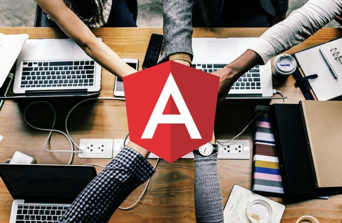 image of 5 people joining hands in a cheer pile over a work desk. the angular logo is in the foreground over their hands