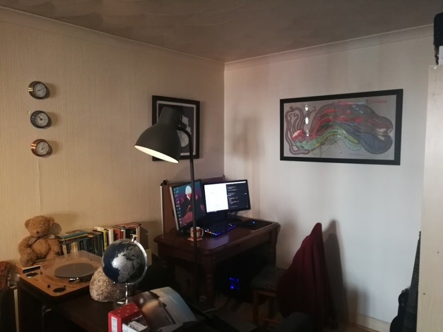 Desk with two monitors in the corner of a room