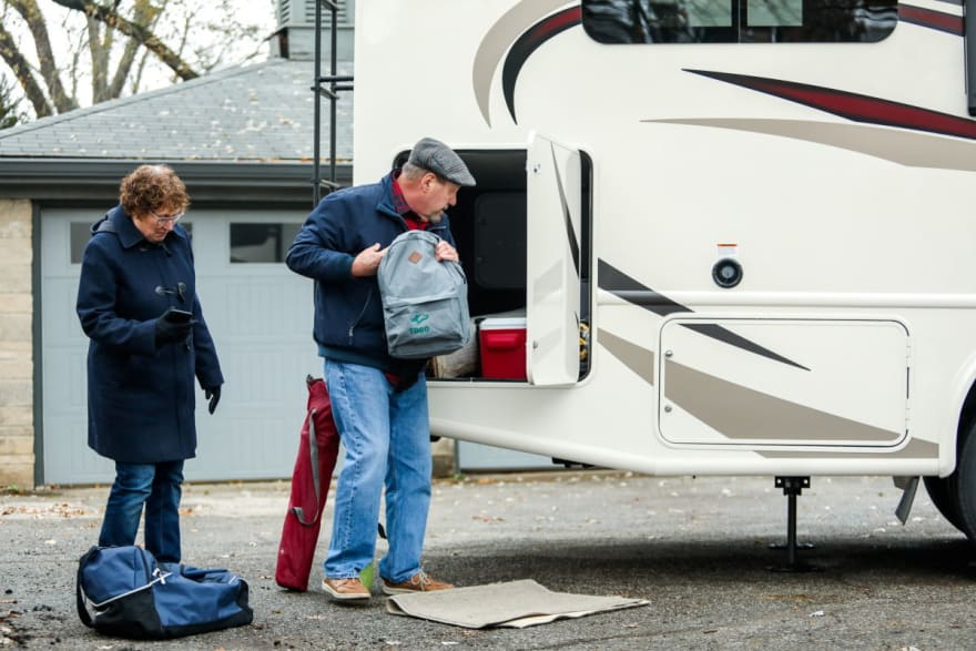 Couple packing luggage into an rv