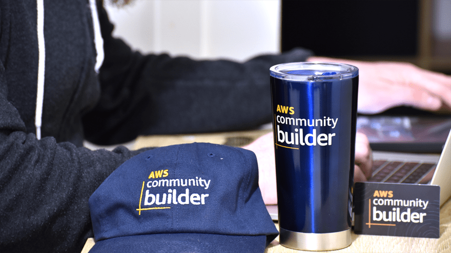 AWS Community Builder Swag laid out on a desk, including a hat, insulated mug, and card