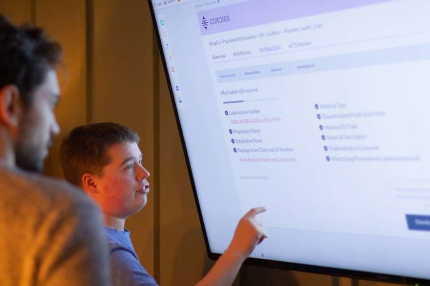 People look at a screen and discuss the layout of the website displayed on it