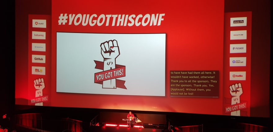 Photo of the conference stage and screen showing the You Got This logo.